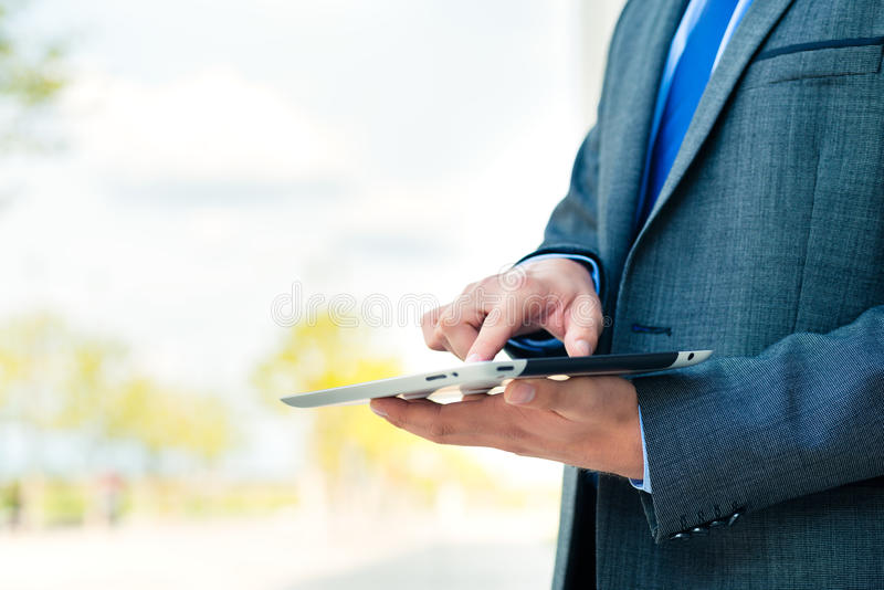 Uomo d'affari facendo uso del computer della compressa immagine stock libera da diritti