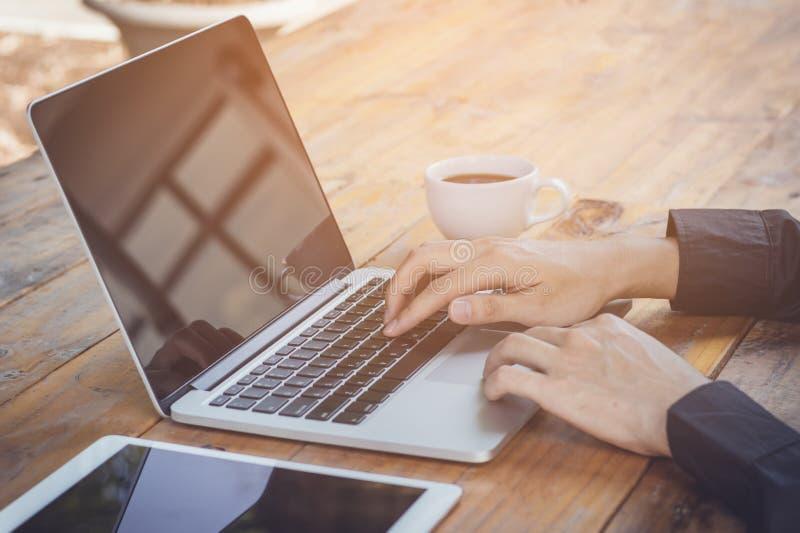 Uomo d'affari facendo uso del computer portatile che funziona con la compressa ed il caffè immagine stock
