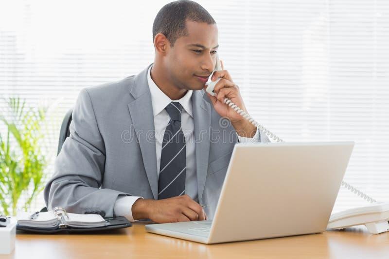 Uomo d'affari facendo uso del computer portatile e del telefono allo scrittorio fotografia stock libera da diritti