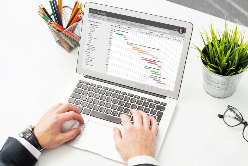 Uomo d'affari facendo uso del software di gestione di progetti sul computer fotografia stock