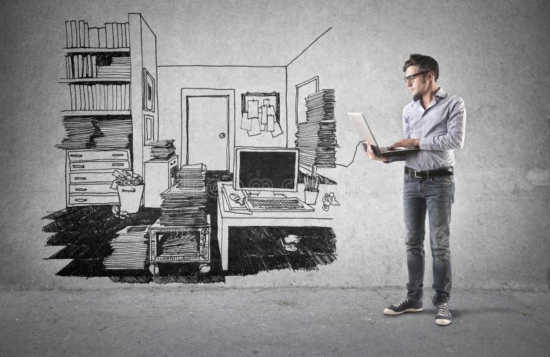 Uomo d'affari facendo uso del suo computer portatile nel suo ufficio immagine stock libera da diritti