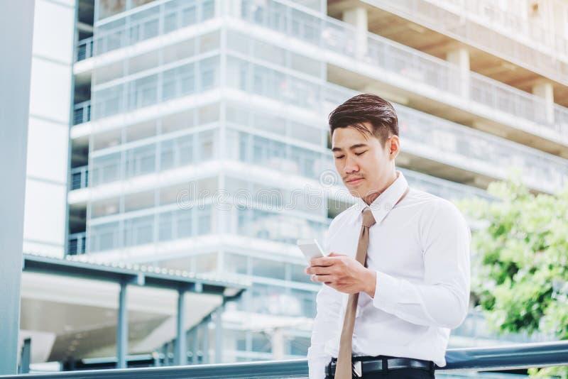 Uomo d'affari facendo uso del telefono e del bere un caffè e dello sguardo della vista a immagine stock