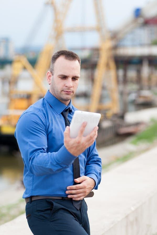 Uomo d'affari facendo uso della compressa digitale all'aperto immagini stock libere da diritti