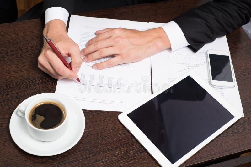 Uomo d'affari facendo uso della compressa digitale con i grafici per la progettazione e l'analisi dei modelli aziendali, partenza fotografia stock