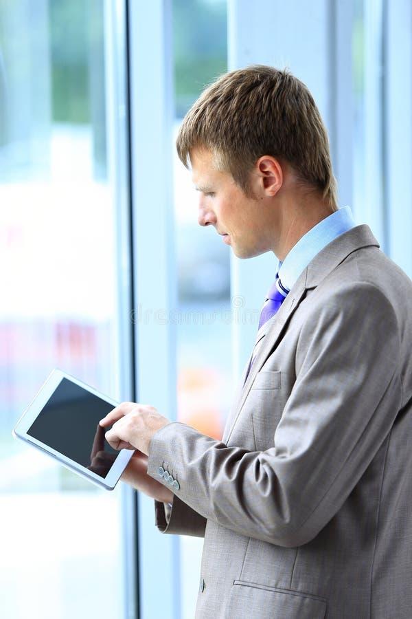 Uomo d'affari facendo uso della sua compressa immagine stock