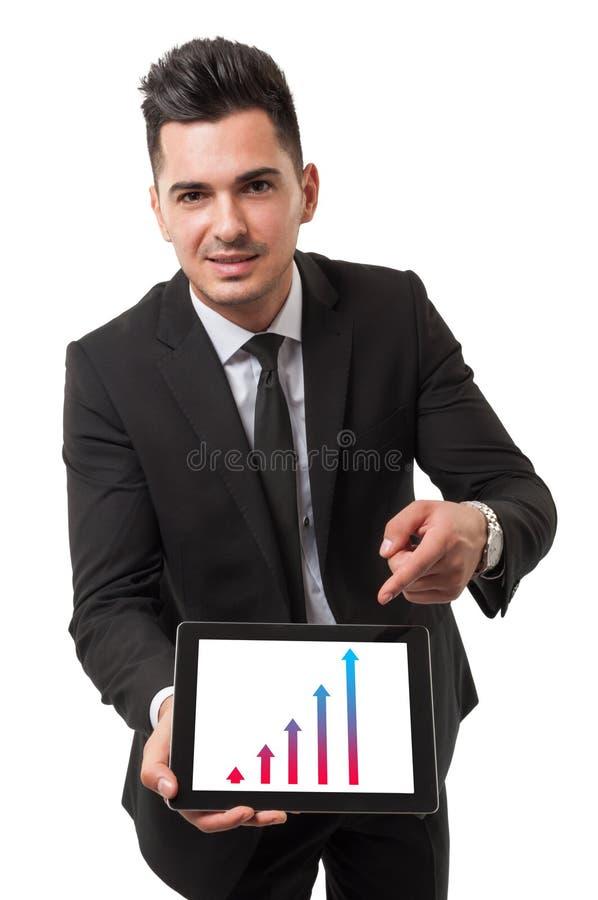 Uomo d'affari facendo uso della sua compressa per mostrare prestazione fotografia stock libera da diritti