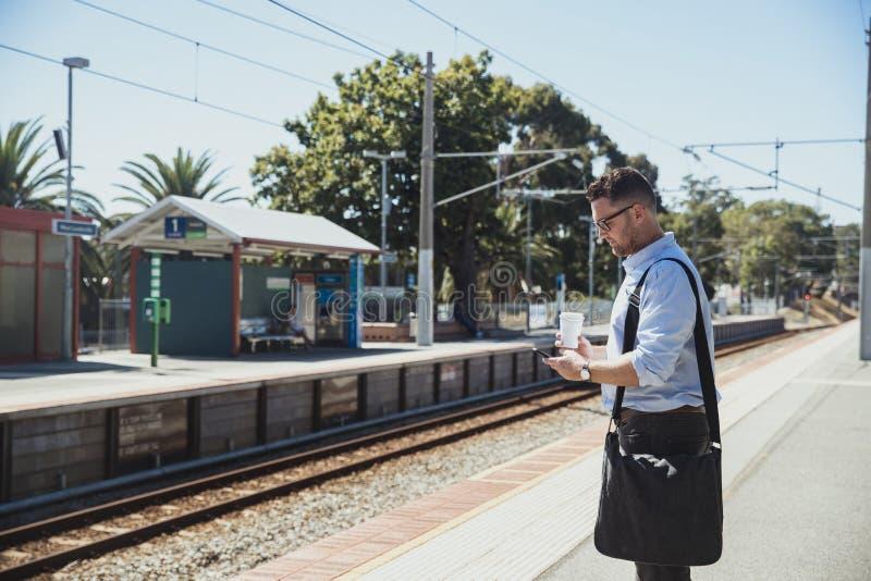 Uomo d'affari facendo uso dello Smart Phone alla stazione ferroviaria immagine stock