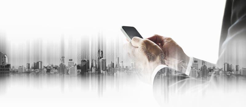 Uomo d'affari facendo uso dello smartphone con la città, concetti di tecnologia della comunicazione di affari immagini stock