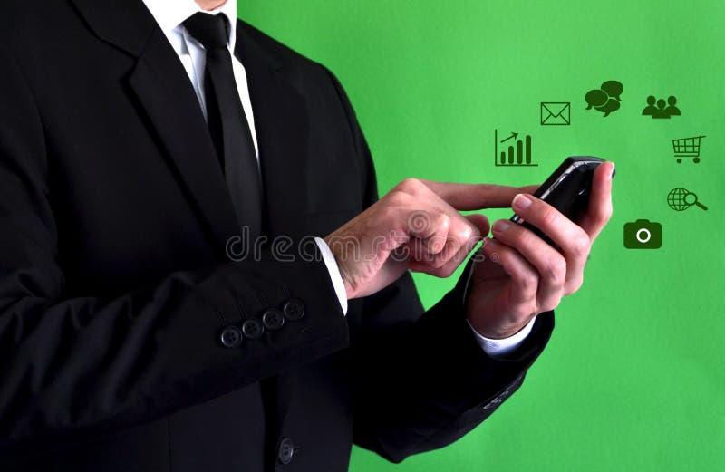Uomo d'affari facendo uso di uno smartphone con le icone virtuali immagini stock libere da diritti