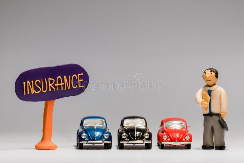 Uomo d'affari fatto da plasticine accanto a tre automobili e ad un segno di assicurazione, su fondo bianco immagini stock
