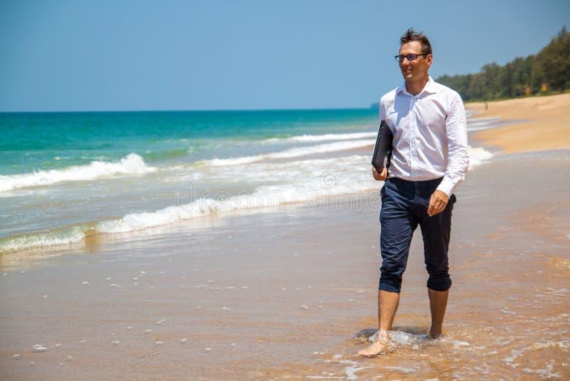 Uomo d'affari felice in camicia con un computer portatile e con i vetri che cammina sulla spiaggia fotografia stock libera da diritti