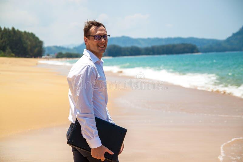 Uomo d'affari felice in camicia con un computer portatile e con i vetri che cammina sulla spiaggia immagini stock libere da diritti
