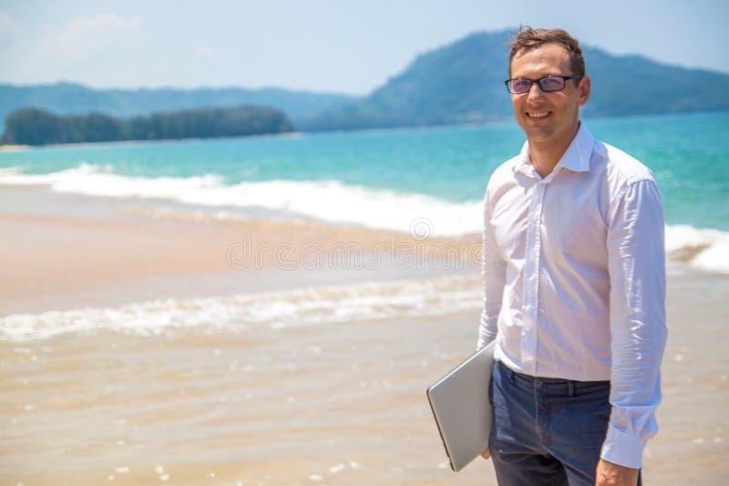 Uomo d'affari felice in camicia con un computer portatile e con i vetri che cammina sulla spiaggia immagine stock libera da diritti