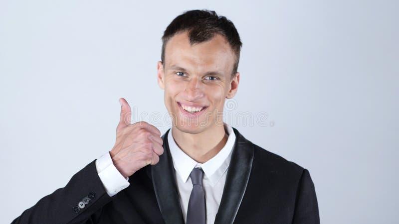 Uomo d'affari felice che dà i pollici fino alla macchina fotografica in studio fotografia stock
