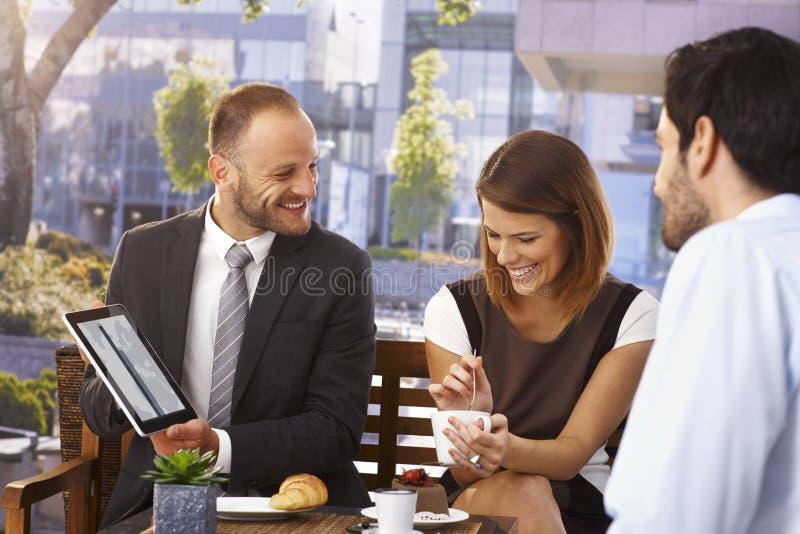 Uomo d'affari felice che fa presentazione alla prima colazione fotografia stock libera da diritti