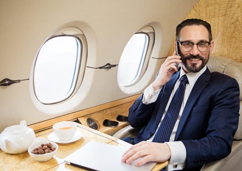 Uomo d'affari felice che ha conversazione dal cellulare fotografia stock