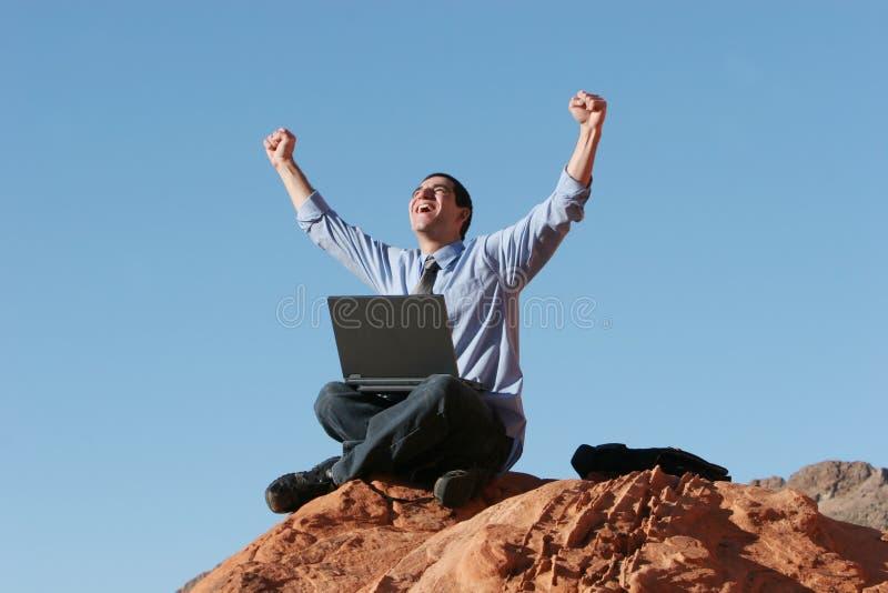 Uomo d'affari felice che lavora al computer portatile immagine stock