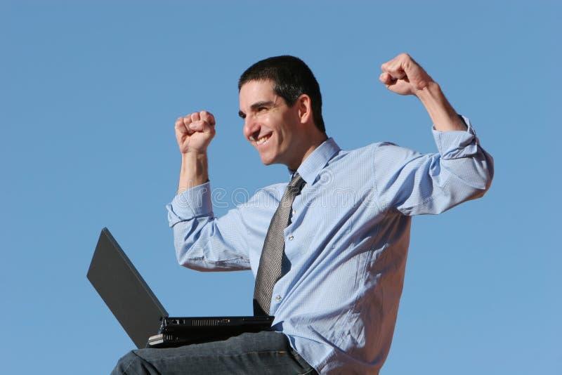 Uomo d'affari felice che lavora al computer portatile fotografie stock libere da diritti