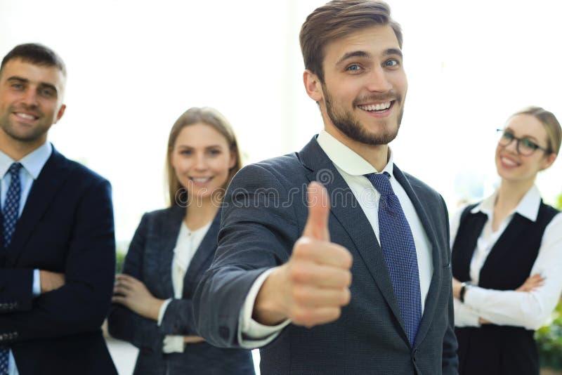 Uomo d'affari felice che mostra il suo pollice su e che sorride mentre i suoi colleghi che stanno nei precedenti fotografie stock