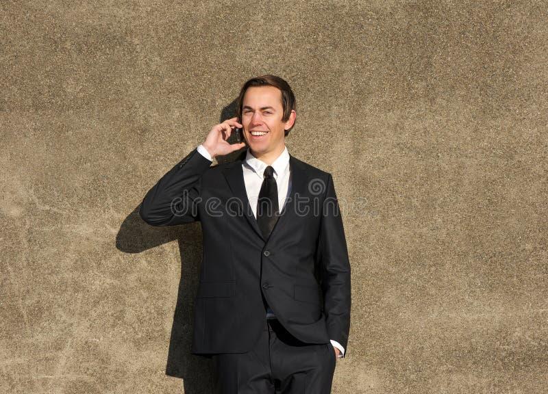 Uomo d'affari felice che parla sul telefono cellulare all'aperto fotografia stock