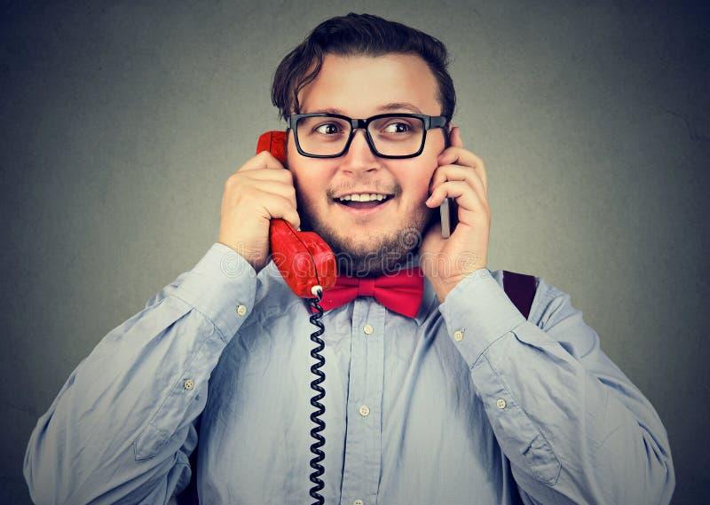 Uomo d'affari felice che per mezzo del cellulare e di retro telefono di stile immediatamente fotografia stock
