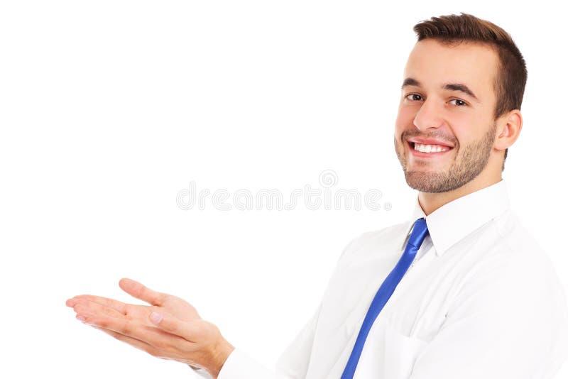 Uomo d'affari felice che presenta qualcosa sopra bianco fotografia stock