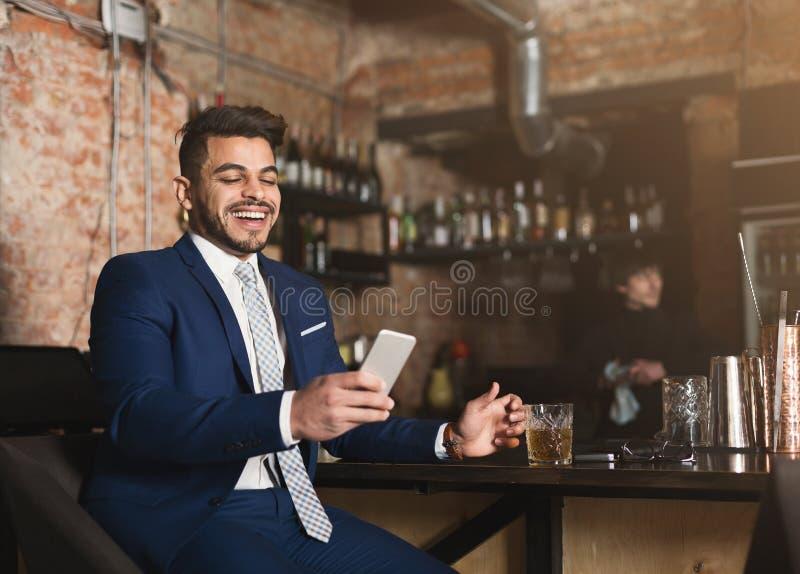 Uomo d'affari felice che riposa nella barra dopo il giorno lavorativo immagini stock
