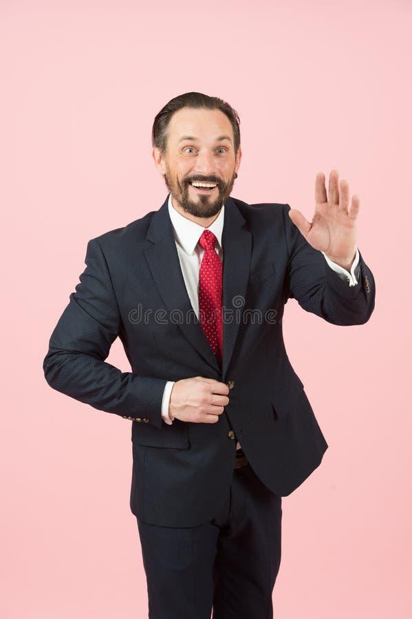 Uomo d'affari felice che saluta sul fondo di rosa pastello Un uomo d'affari bello è accogliente o dicente il ciao i suoi partner fotografia stock libera da diritti