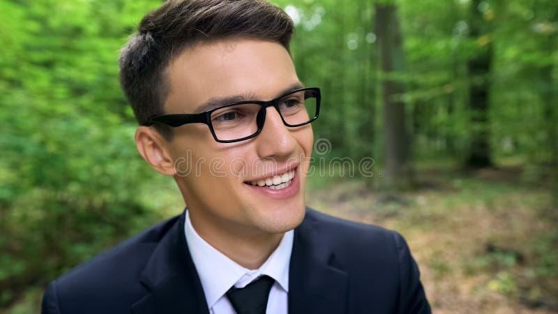 Uomo d'affari felice che sorride nella foresta, sognando per smettere viaggio di inizio e di lavoro fotografia stock libera da diritti