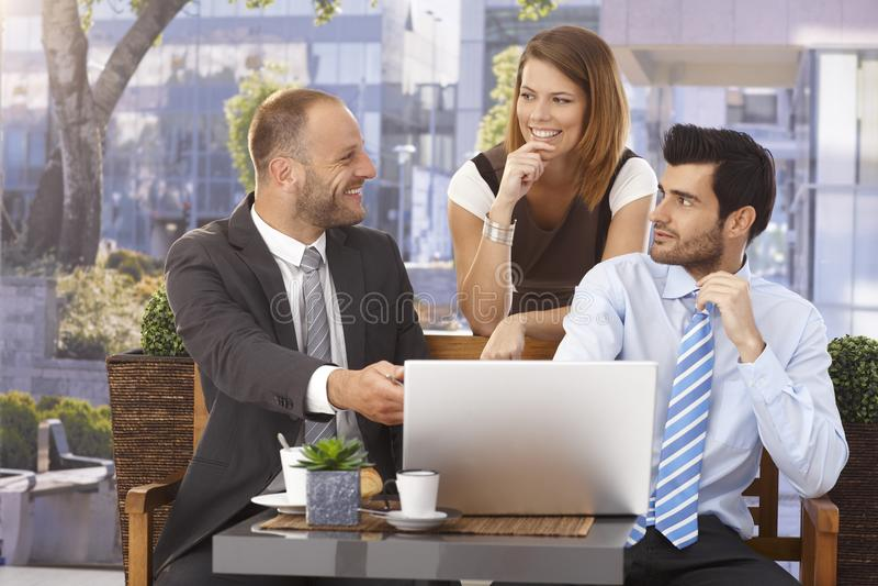 Uomo d'affari felice che spiega progetto sul computer portatile immagini stock libere da diritti