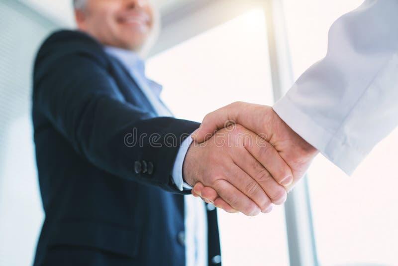 Uomo d'affari felice che stringe le mani con il medico immagine stock libera da diritti