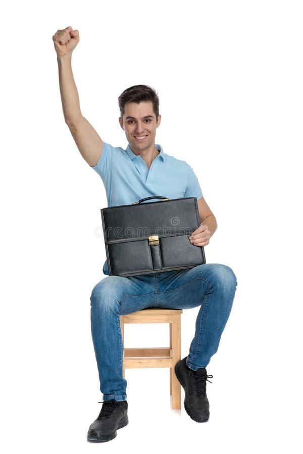 Uomo d'affari felice che tiene la sua cartella e che celebra immagine stock libera da diritti