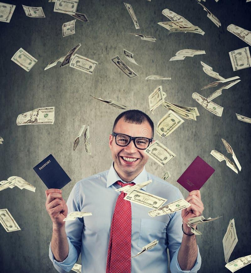 Uomo d'affari felice con due passaporti sotto la pioggia dei soldi immagine stock libera da diritti