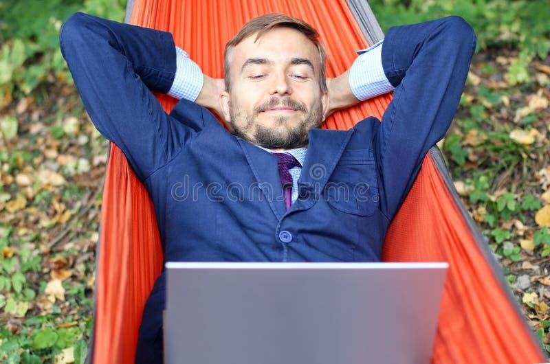 Uomo d'affari felice con i relaxs del computer portatile in un'amaca sulla natura Fre fotografia stock