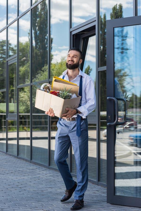 Uomo d'affari felice con la scatola di cartone che cammina fuori edificio per uffici fotografia stock libera da diritti