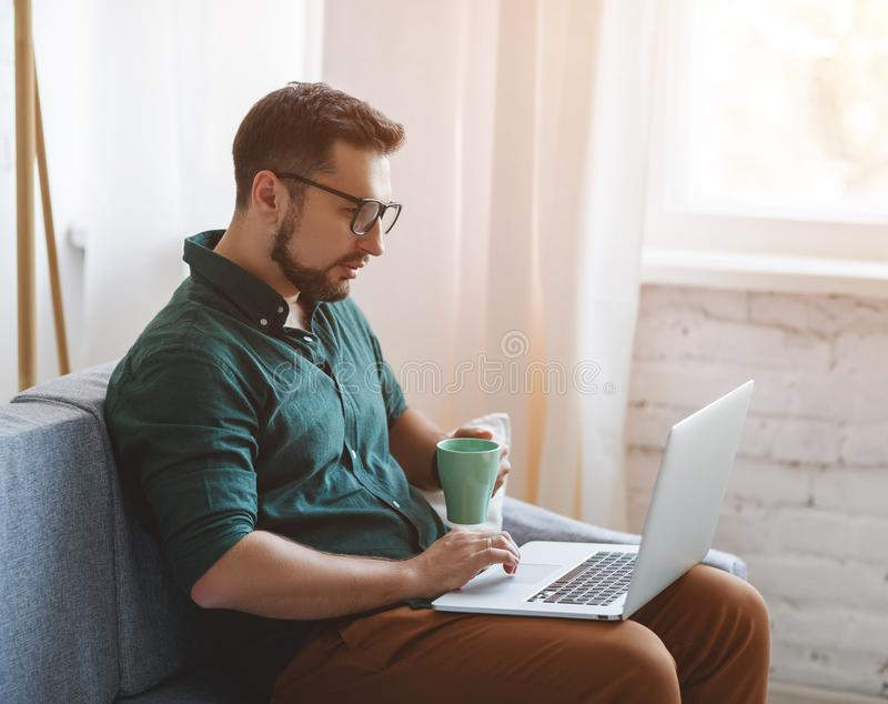 Uomo d'affari felice dell'uomo, free lance, studente che lavora al computer a immagini stock libere da diritti