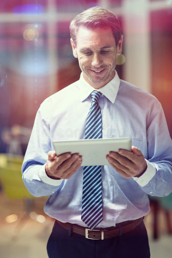 Uomo d'affari felice facendo uso della compressa digitale fotografia stock
