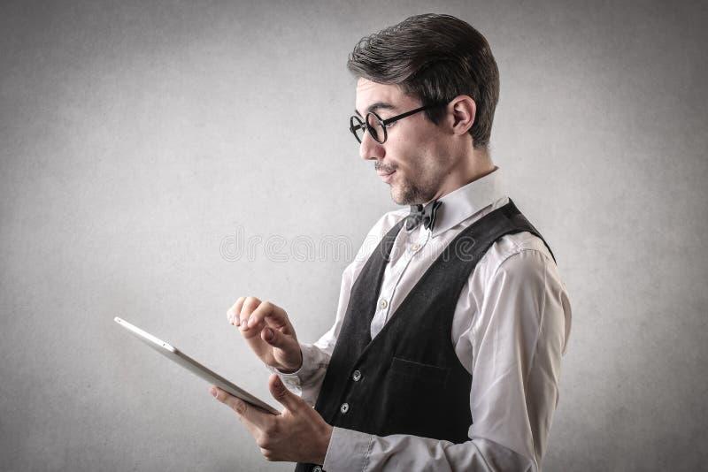 Uomo d'affari felice facendo uso di una compressa fotografie stock