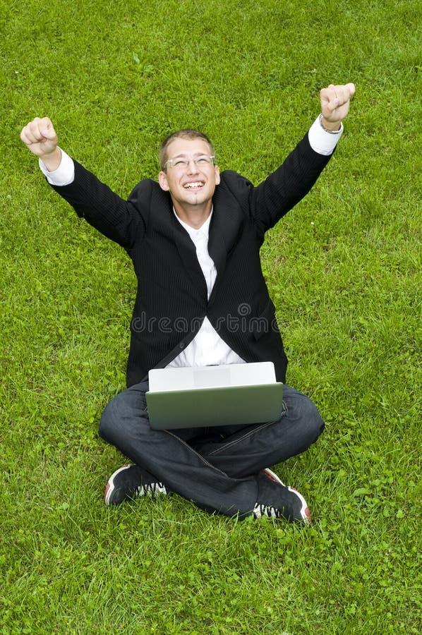 Uomo d'affari felice sull'erba con il computer portatile immagini stock