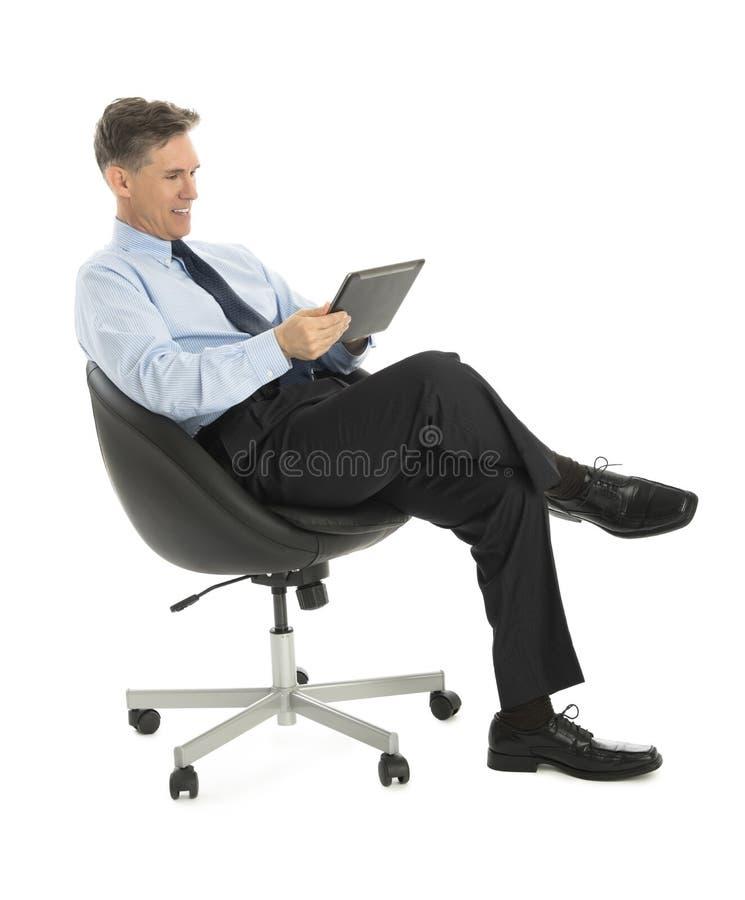 Uomo d'affari felice Using Tablet Computer mentre sedendosi sull'ufficio immagine stock
