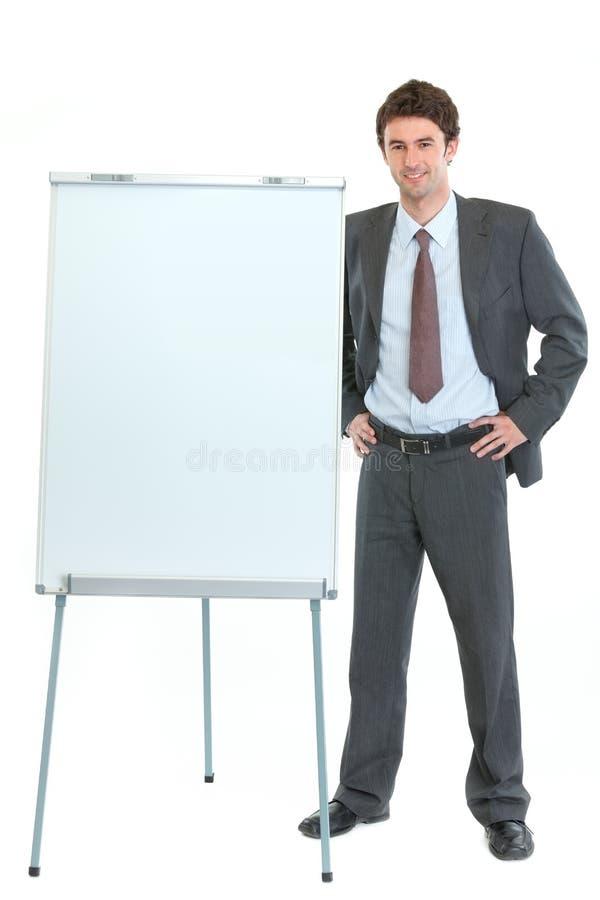 Uomo d'affari felice vicino al basamento del flipchart fotografie stock libere da diritti