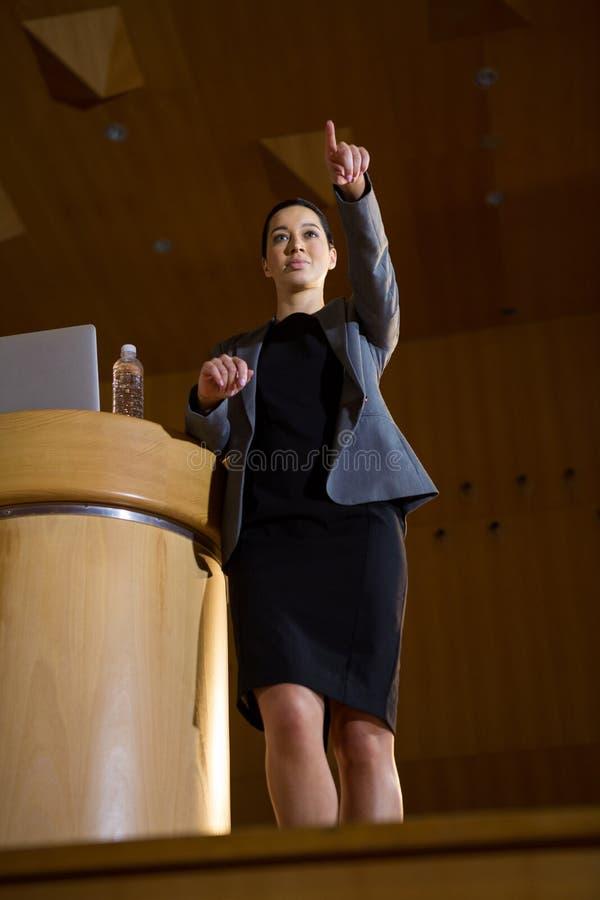 Uomo d'affari femminile che indica mentre dando un discorso immagini stock