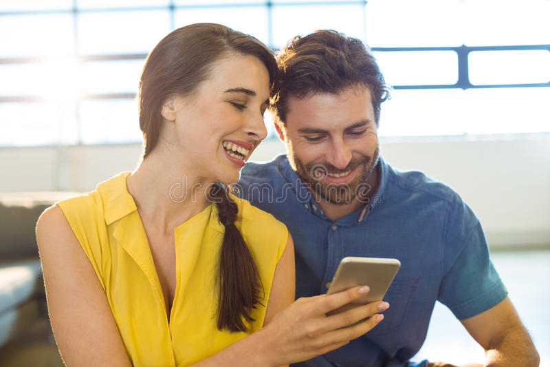 Uomo d'affari femminile che mostra telefono cellulare al collega fotografia stock libera da diritti