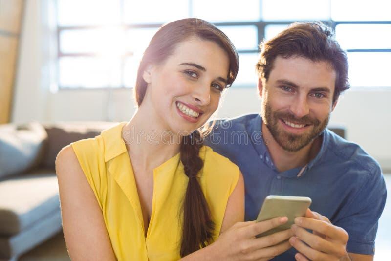 Uomo d'affari femminile che mostra telefono cellulare al collega fotografie stock