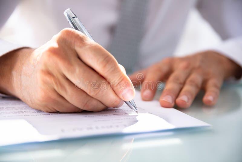 Uomo d'affari Filling Contract Form fotografia stock