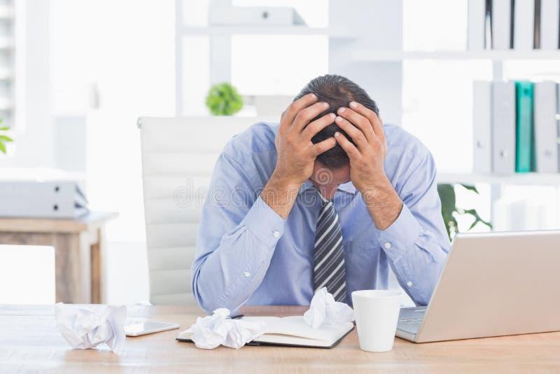 Uomo d'affari frustrato che lavora nel suo ufficio fotografie stock libere da diritti