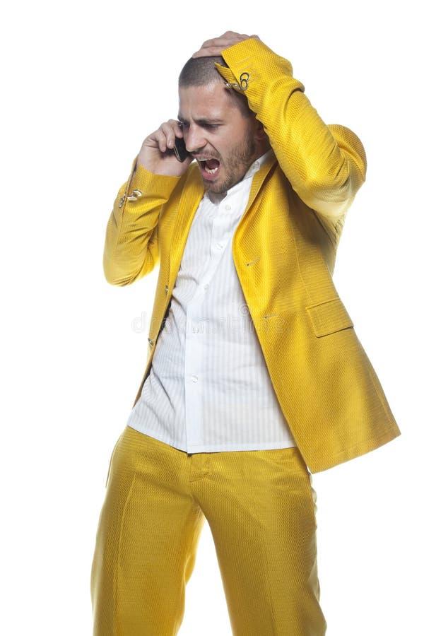 Uomo d'affari frustrato che parla sul telefono, uomo di affari isolato sui precedenti fotografie stock