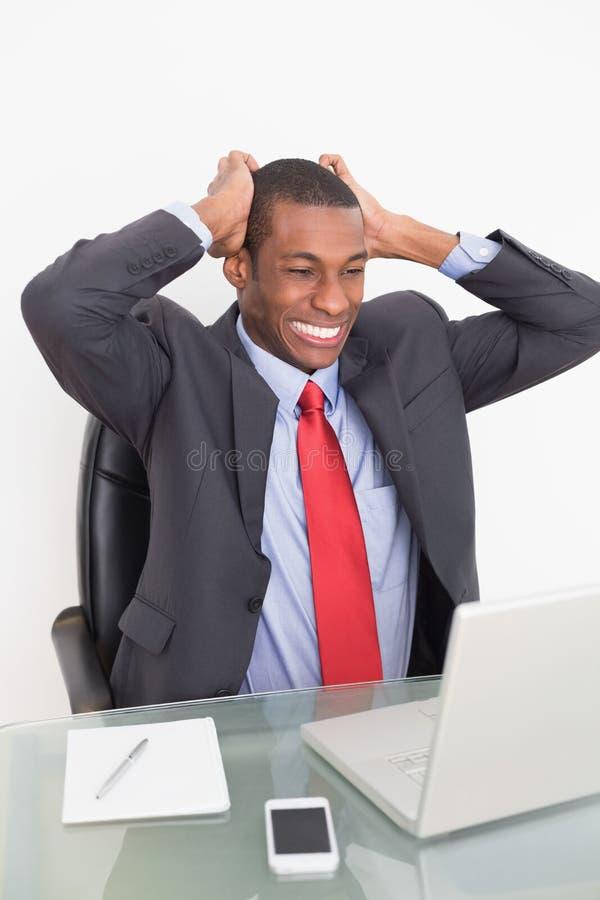 Uomo d'affari frustrato di afro che esamina computer portatile lo scrittorio fotografie stock