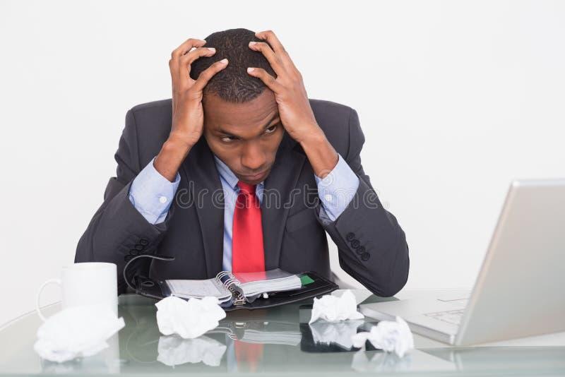 Uomo d'affari frustrato di afro con la testa in mani allo scrittorio immagini stock