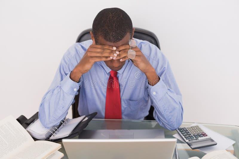 Uomo d'affari frustrato di afro con la testa in mani allo scrittorio immagine stock libera da diritti